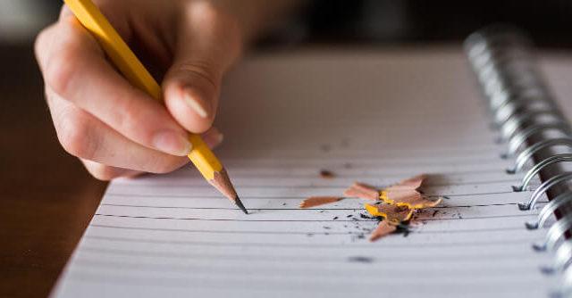 ノートに鉛筆で文字を書いている画像