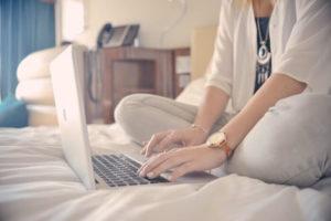 ベッドの上でブログを書いている女性