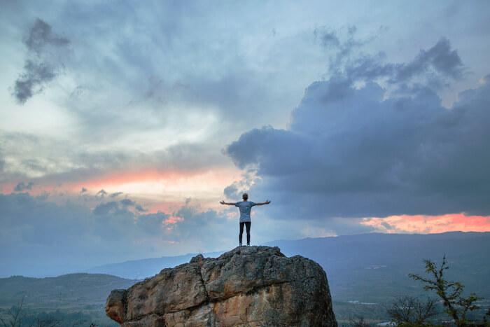 崖で両手を広げている男性